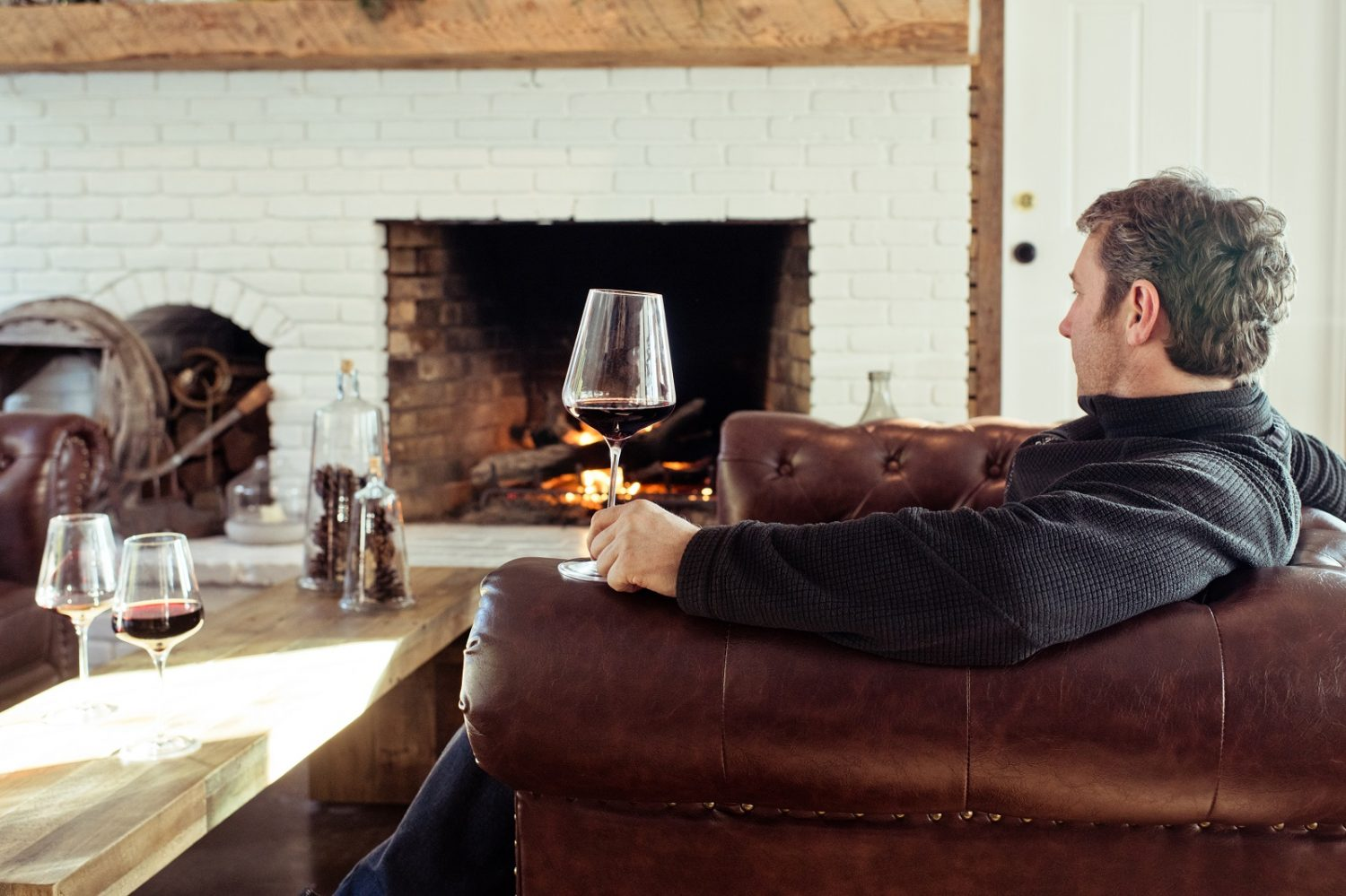 Man drinking wine in front of fire