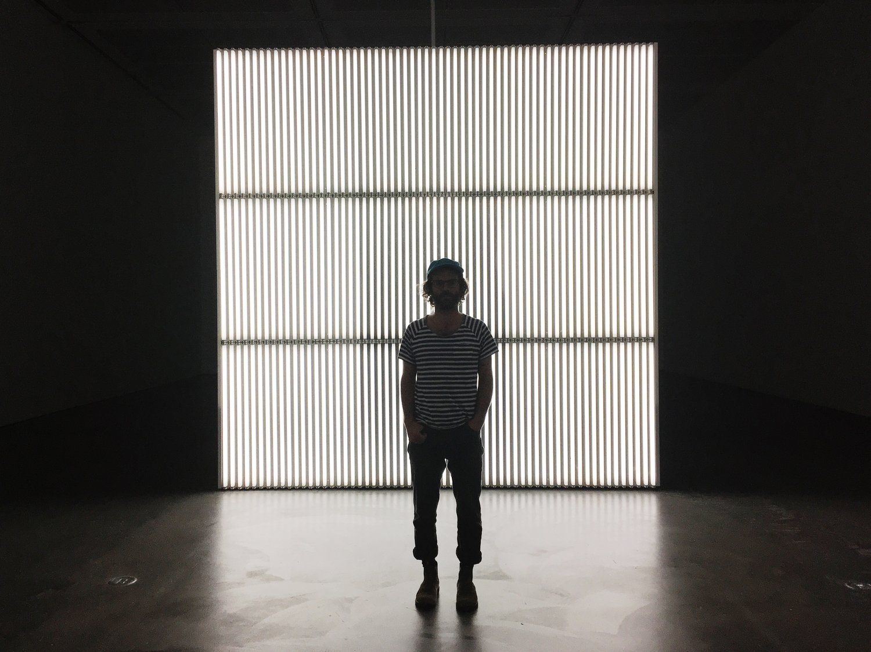 Uncommon Art Artist Sean Spellman standing in front of wall of lights